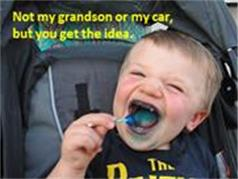 Child eating lollipop in carseat