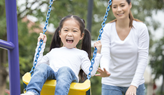 Image of a girl on a swing with her mom pushing from behind